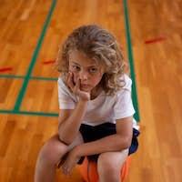 Sad school girl sitting on basketball and looking at the camera on basketball court at school
