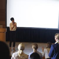 Beautiful businesswoman thanking the audience while finished her presentation in auditorium