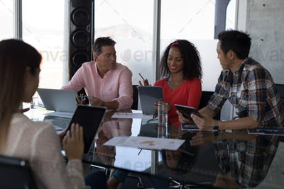 Front view of multi-ethnic business executives working on table in conference room at office