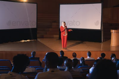 Businesswoman standing and giving presentation in auditorium while holding mike in her hand