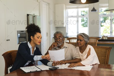 Female real estate agent and senior couple discussing over documents at the table of the living room