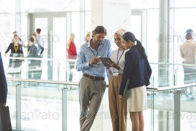 Front view of young diverse business executives discussing over digital tablet in office lobby