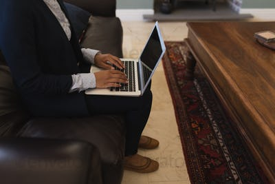 Female real estate agent using laptop while sitting on the sofa in living room