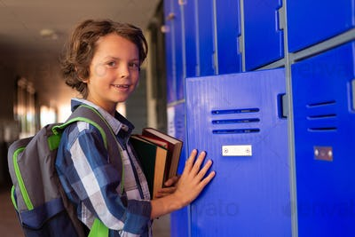 Front view of a cute Caucasian schoolboy closing the locker in the locker room at school