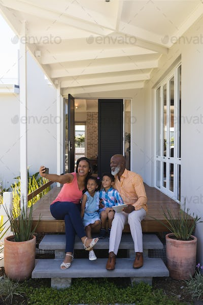 Happy African American multi-generation family taking selfie with mobile phone in the porch