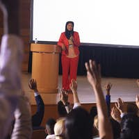 Mixed race businesswoman standing around the podium in the auditorium while audience raising hand