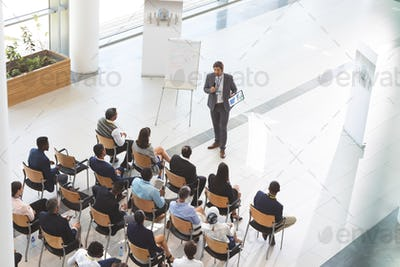 Man speaker with digital tablet speaks in a business seminar in front of diverse business people