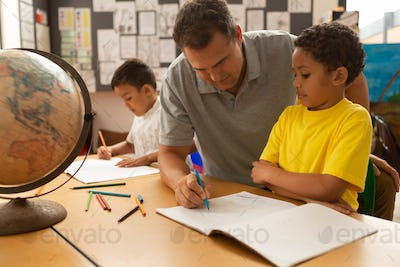 Handsome Caucasian male teacher teaching a cute mixed-race schoolboy to draw