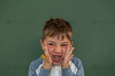 Caucasian schoolboy with hands on face and surprised against greenboard in a classroom
