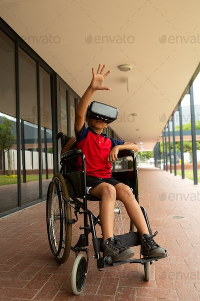 Mixed-race disabled schoolboy using virtual reality headset with one hand in the air in corridor