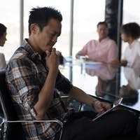 Young Asian male executive using digital tablet in office with colleagues working in the background