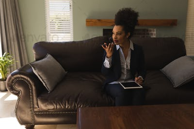 African American female real estate agent talking on mobile phone while using digital tablet