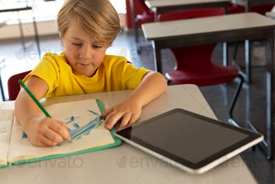 High angle view of boy drawing sketch on notebook at desk in a classroom at elementary school