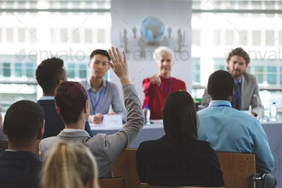 Well dressed businesswoman raising hand in business seminar in office building