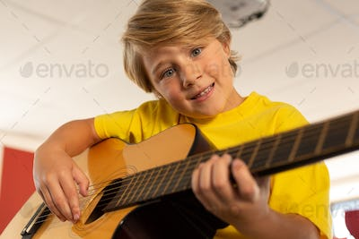 Caucasian boy looking at camera while playing guitar in a classroom