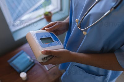 Mid section of African American female doctor holding blood pressure monitor at home