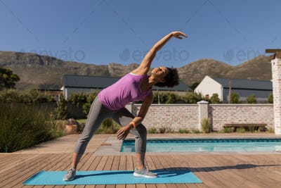 Young African American woman performing stretching exercise next to the swimming pool
