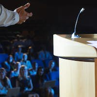 Rear view of businessman giving presentation in front of audience in auditorium