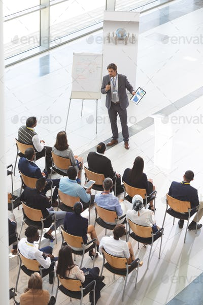 Businessman speaking while holding digital tablet and microphone at conference.