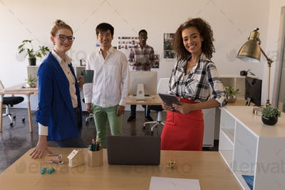 Portrait of young diverse business colleagues standing together in modern office