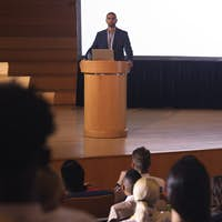 Front view of handsome mixed race businessman giving speech in front of audience in the auditorium