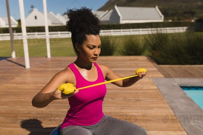Beautiful young African American woman exercising with resistance band in the backyard