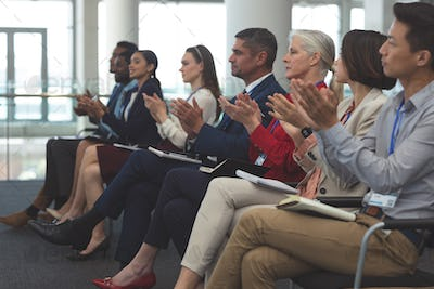 Side view of diverse business people applauding in a business seminar in office building