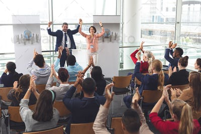 Diverse business people applauding in front of diverse business executives holding arms up