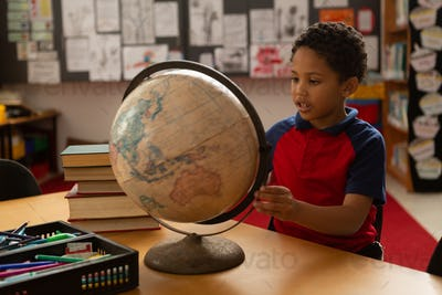 Front view of mixed-race schoolboy studying globe at desk in a classroom at elementary school