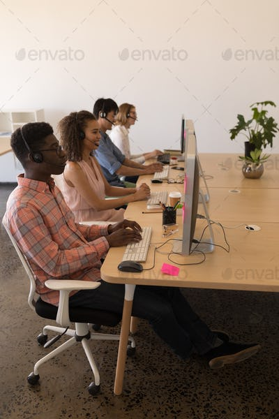 Young diverse executives working on personal computer while communicating on headset