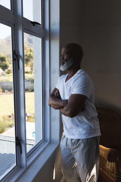 Thoughtful handsome senior African American man looking through the window witch crossed arms