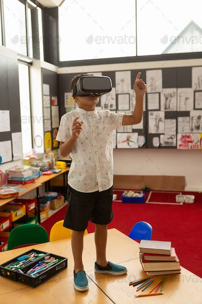 Cute mixed-race schoolboy using virtual reality headset on a desk in classroom