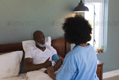 Young female doctor measuring blood pressure of senior man at home