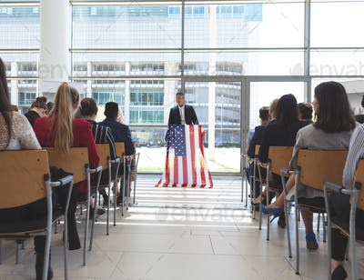 Male speaker speaks in a business seminar in office building with american flag on his mic stand