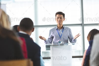 Front view of young Asian businessman speaking at business seminar in office building
