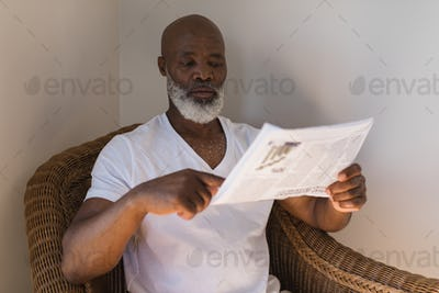 Front view of a handsome senior African American man reading newspaper on a wicker chair at home