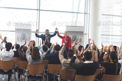 Diverse business people applauding and celebrating at business seminar