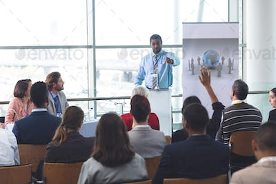Rear view of mixed race businesswoman raising hand during business seminar in modern office building