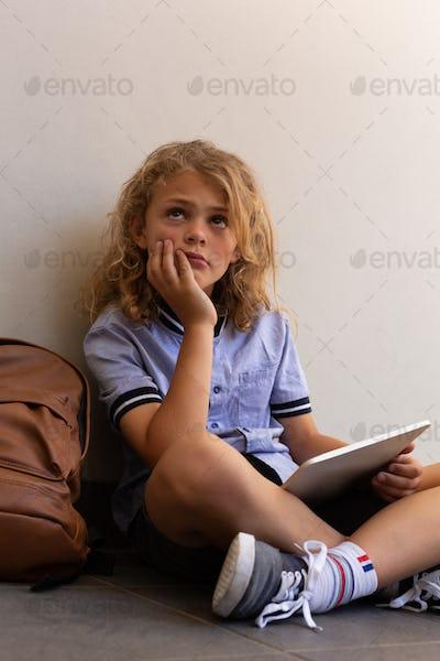 Schoolgirl with a digital tablet and a school bag sitting on the floor in school corridor