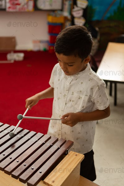 Schoolboy playing xylophone in a classroom at elementary school