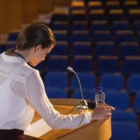 Businesswoman looking in script  and trying to speak in the empty auditorium