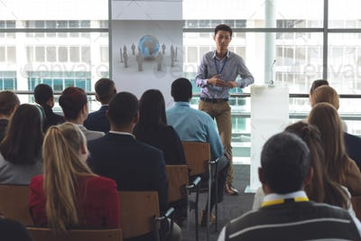 Young businessman speaking in front of business professionals at business seminar in office building