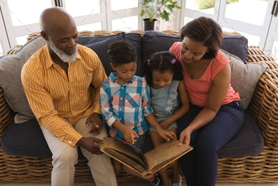 Happy multi-generation family reading a story book in living room at home