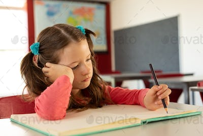 Front view of sad pretty Caucasian girl writing on notebook in a classroom at elementary school