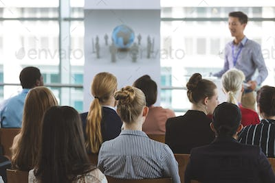 Group of business professionals attending a seminar with an male Asian speaker in office building