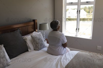 Rear view of worried senior African American woman relaxing in bedroom at home