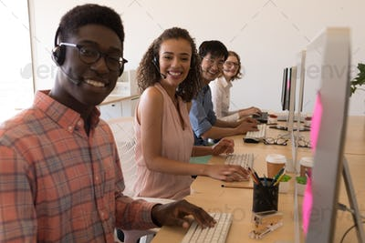 Young diverse executives working on personal computer while communicating on headset in office