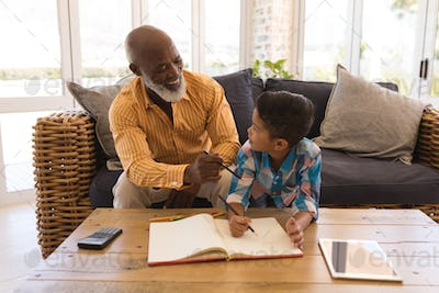 Proud grandfather helping his grandson with homework in living room at home