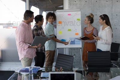 Business colleagues discussing about the strategy on the flip chart board in modern office
