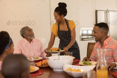 Front view of African American woman serving food to her family on dining table at home